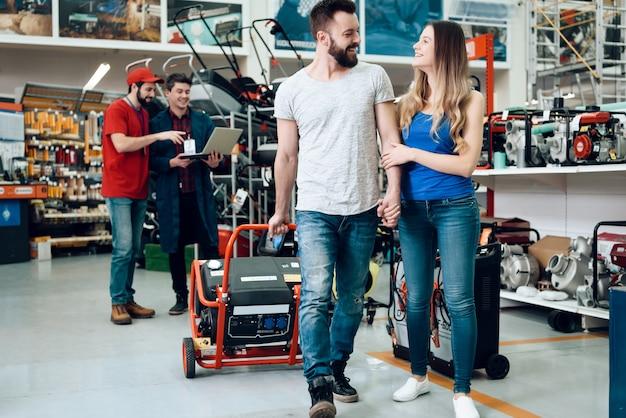 セールスマンは、顧客のカップルに新しい発電機を見せています。