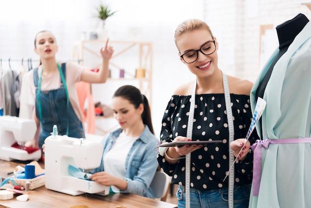 若いデザイナーが新しいドレスと笑顔を見ています。