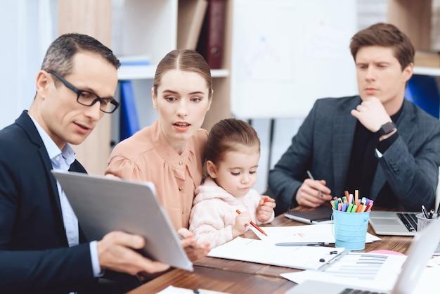 Мужчина показывает женщине с ребенком что-то на планшете.