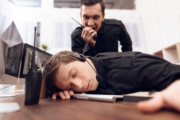 若い男の警備員が職場で眠っています。