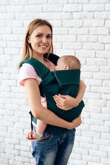 ベビースリングで生まれたばかりの赤ちゃんを持つ母親を笑顔。