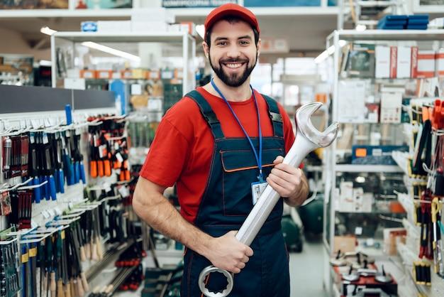 セールスマンは店で新しい巨大なレンチでポーズをとっています。