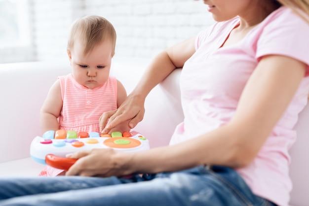 かわいい赤ちゃんが母親と一緒にソファーでおもちゃを遊んで。