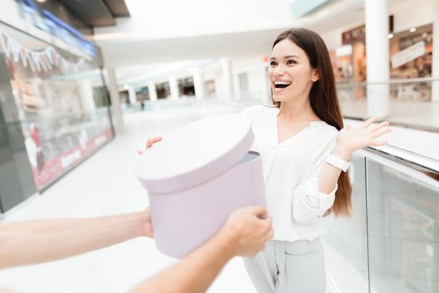 男は購入と新しいラウンドボックスを女性に提示します。