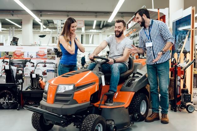 Продавец показывает пару клиентов новую уборочную машину.