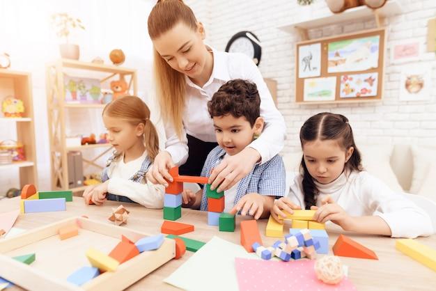 木製の立方体と先生と遊んでいる子供たちは彼らを助けています。
