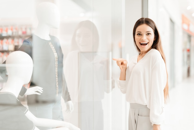 女の子は新しいドレスを見て店の窓の近くに立っています。