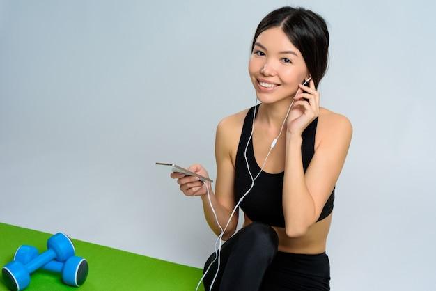 スポーツスーツの女の子は、ヘッドフォンで音楽を聴きます。