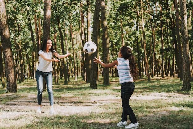 Молодая мать бросает мяч с дочерью.