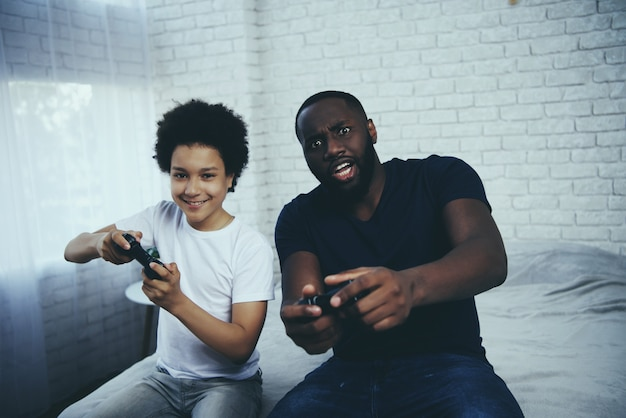 アフリカ系アメリカ人の父親が息子と一緒にビデオゲームをしています。