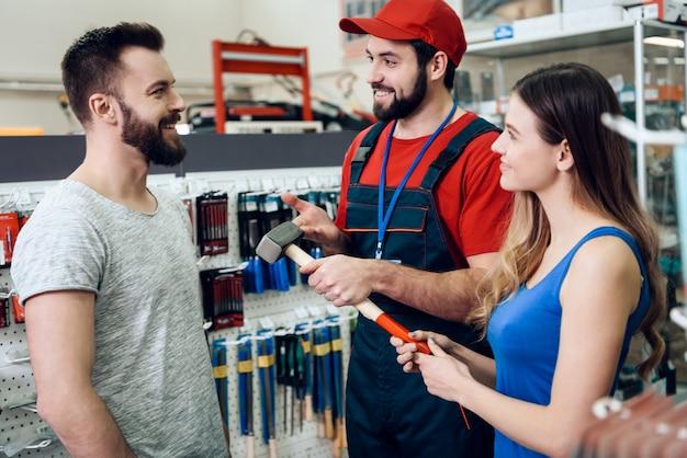 セールスマンはクライアントに新しいラバーハンマーを見せています