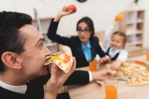 ビジネスマンの若い家族が家で昼食をとります。