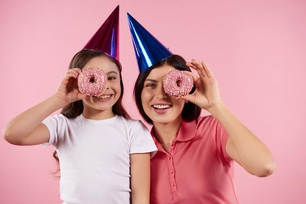 Счастливая мать и дочь в праздничных шапках