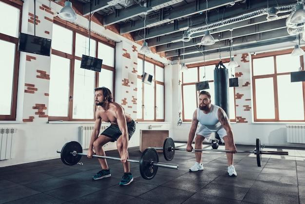 Два мощных парня в тренажерном зале поднимают штанги.
