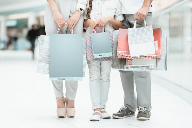 買い物袋を持つ娘を持つ人々がショッピングモールにいます。