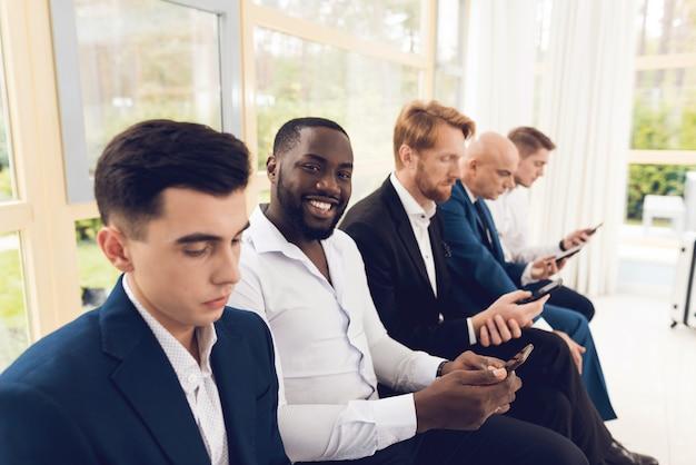Мужчины в костюмах сидят в зрительном зале на аэродроме.