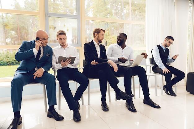 Мужчины в костюмах сидят в зале ожидания в аэропорту.