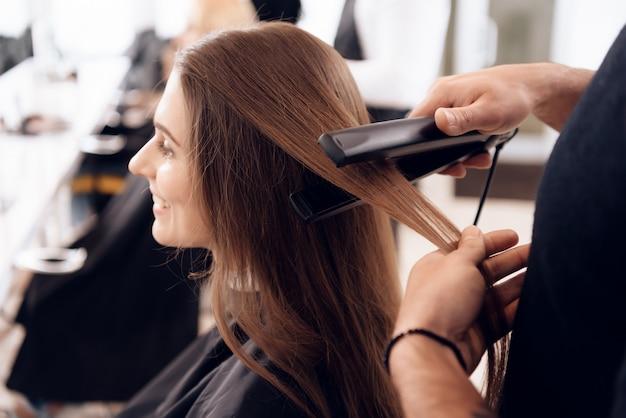 Стилист выпрямляет каштановые волосы женщины.