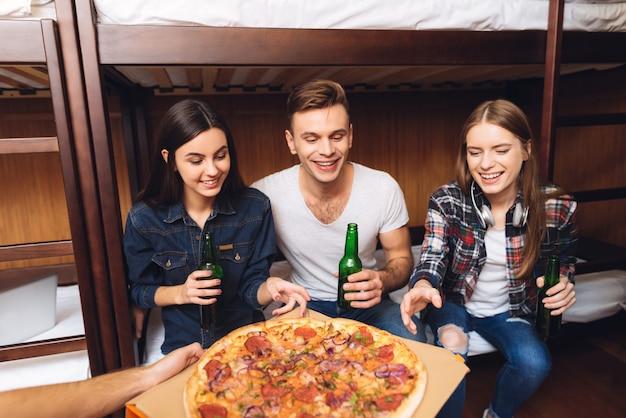 男のクールな写真が友達にピザをもたらしました。