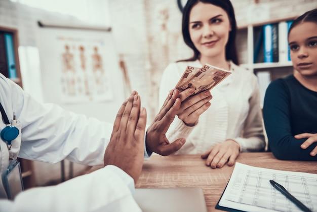 女性は診療所で医者を買収しようとします。