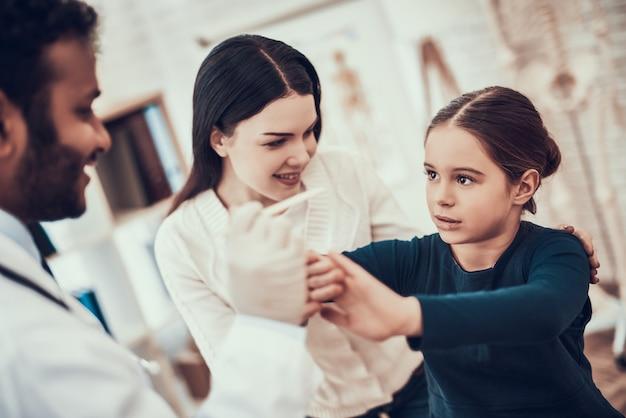 医者は女の子ののどを調べようとしています。