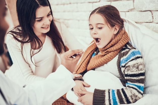 医者は妊娠中の母親を持つ少女の喉を調べています。
