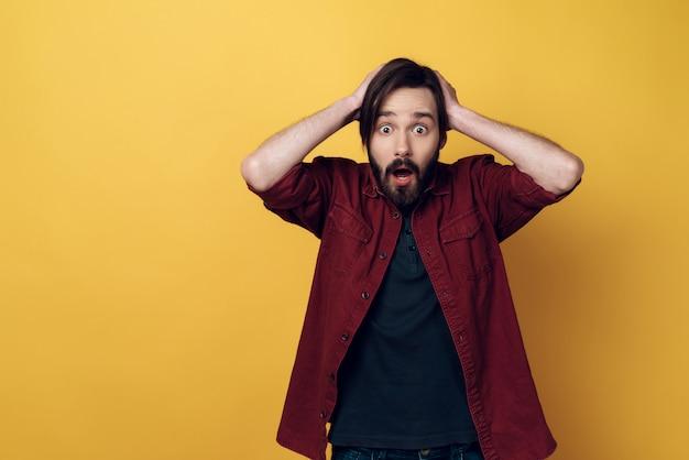 Портрет обеспокоенного молодого бородатого мужчины держит голову