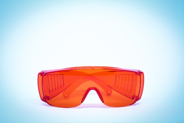 背景やテクスチャのプラスチック製の赤い防水メガネ。