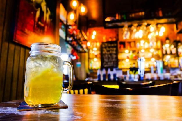 オレンジジュースがカウンターバー、オレンジ色の光と木製の前景-インテリアのコンセプトを持つテーブルに設定。
