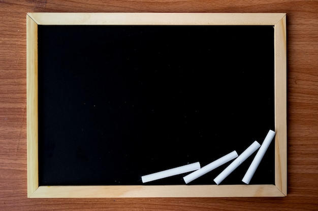 汚れた黒板とコンテンツ-テクスチャ、背景、暗いトーンのコンセプトのためのスペースを持つ木製フレームの黒板。