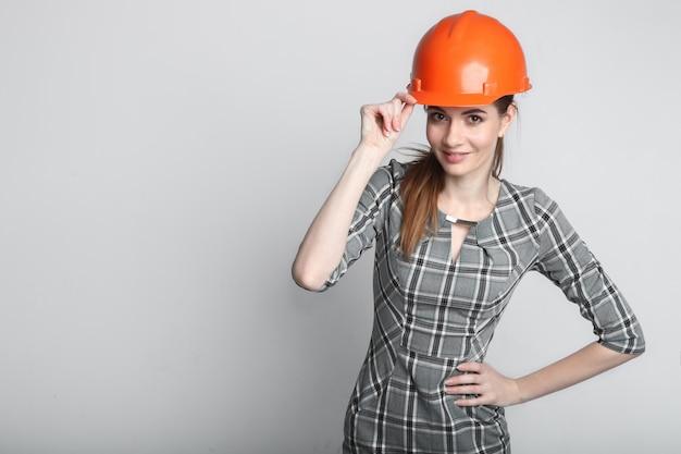 白で隔離ビルダーヘルメットを着て笑顔のビジネス女性の肖像画