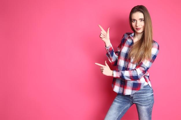 Милая усмехаясь девушка в в рубашке и джинсах стоя на розовой предпосылке. образ жизни, эмоциональный, в стиле фанк. леди показывает указательными пальцами обеих рук в сторону