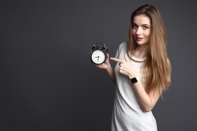 灰色の背景に目覚まし時計を指して若いスリムな女性