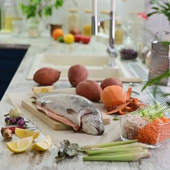 台所のテーブルで野菜を調理するための生の魚。