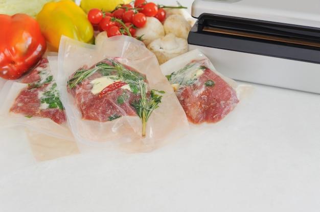 Три сырых стейка в вакуумной упаковке и вакуумном упаковщике. су-вид, новые технологии кухни.