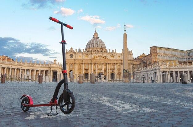 イタリア、ローマのバチカンを背景にした赤いプッシュスクーター。