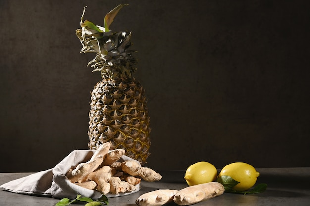 Имбирь, ананас и лимон на черном