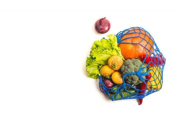 野菜がいっぱい詰まったメッシュのテキスタイルバッグ。健康食品と廃棄物ゼロのコンセプト。白で隔離。