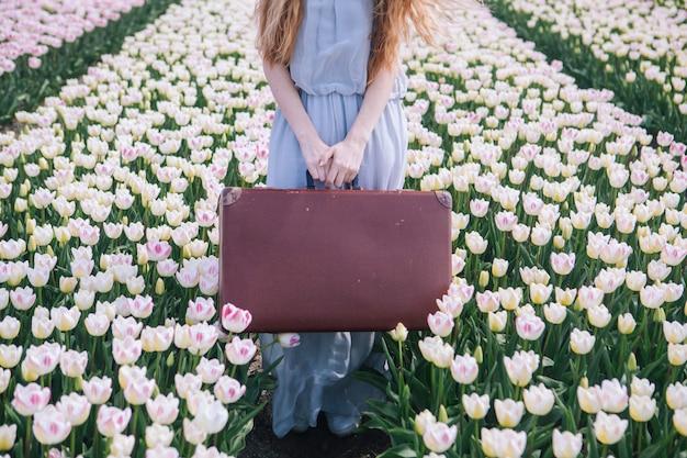 Красивая молодая женщина при длинные красные волосы нося в белом платье стоя с старым винтажным чемоданом на красочном поле тюльпана.