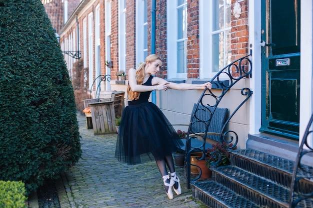 バレエ衣装とトウシューズの赤い髪の若いバレリーナの女性は、通りで踊る美しいポーズです。