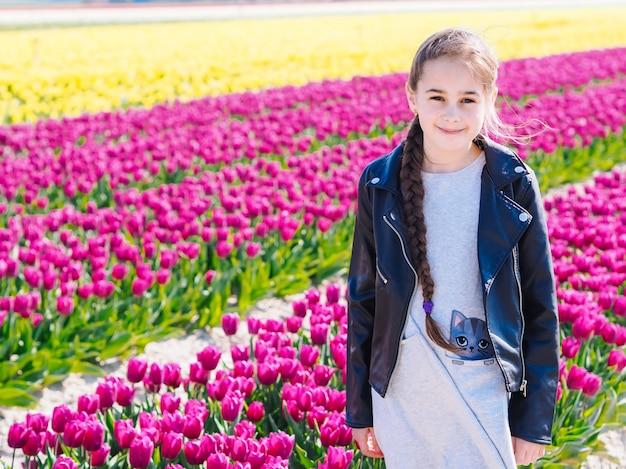 Милая девочка с длинными волосами на полях тюльпанов