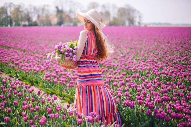 Красивая рыжеволосая женщина в полосатом платье и держит букет тюльпанов в корзине