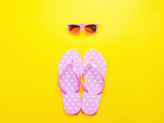 夏は平らに置きました。ビーチアクセサリーピンクビーチサンダルと黄色の背景にサングラス。