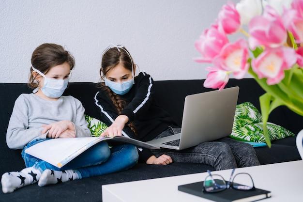 オンライン教育、遠隔教育、ホームスクーリング。ノートパソコンのタブレットで自宅でオンラインレッスン中に宿題を勉強し、ビデオ通話を保持している子供たち。検疫上の社会的距離。自己隔離