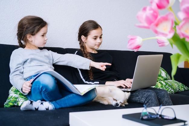 Онлайн обучение, дистанционное обучение, обучение на дому. дети изучая домашнюю работу во время онлайн урока дома в таблетке компьтер-книжки и держа видеозвонок. социальная дистанция на карантине. самоизоляция