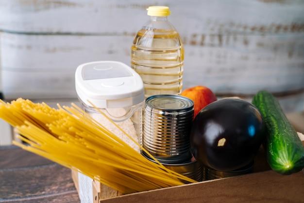 Продовольственные поставки кризис продовольственный запас на период изоляции карантин коронавирус в желтой стене. различная еда в алюминиевых банках, рис, макароны. доставка еды, пожертвование. вид сверху. копировать пространство