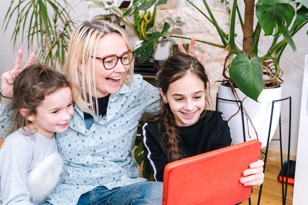 家で座っているとビデオ通話を保持している子供を持つ女性。友人や家族とのビデオ通話にスマートフォンを使用している家族。人々はビデオを介して通信します-カメラを見て挨拶の手を振っています
