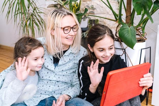 Женщина с детьми, сидя у себя дома и проведение видеозвонков. семья, используя смартфон для видео-звонка с другом или семьей. люди общаются через видео - смотрящую камеру и машут руками приветствия