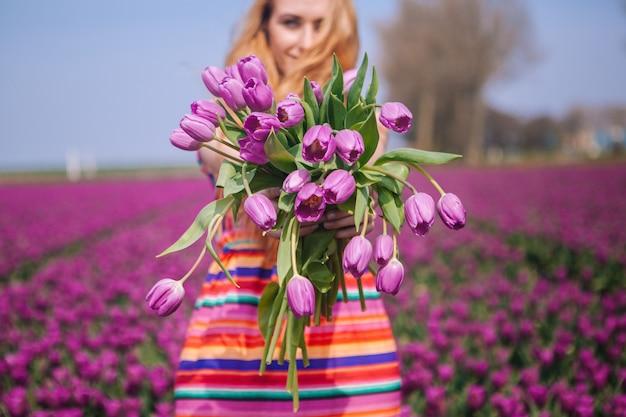 Рыжеволосая женщина в платье держит корзину с букетом цветов тюльпанов