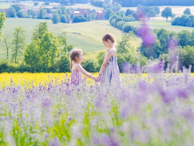 Две маленькие девочки в сиреневом поле